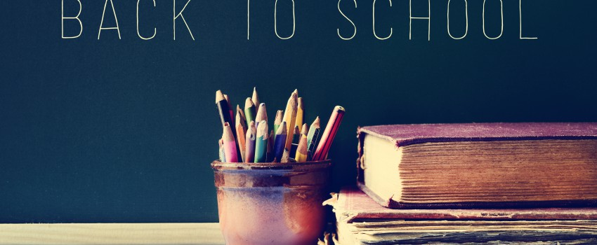 pencils, old books and the text back to school on a chalkboard, filtered